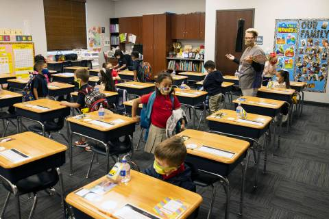 Susan Villagracia, kindergarten teacher, directs her student where to sit during the first day ...