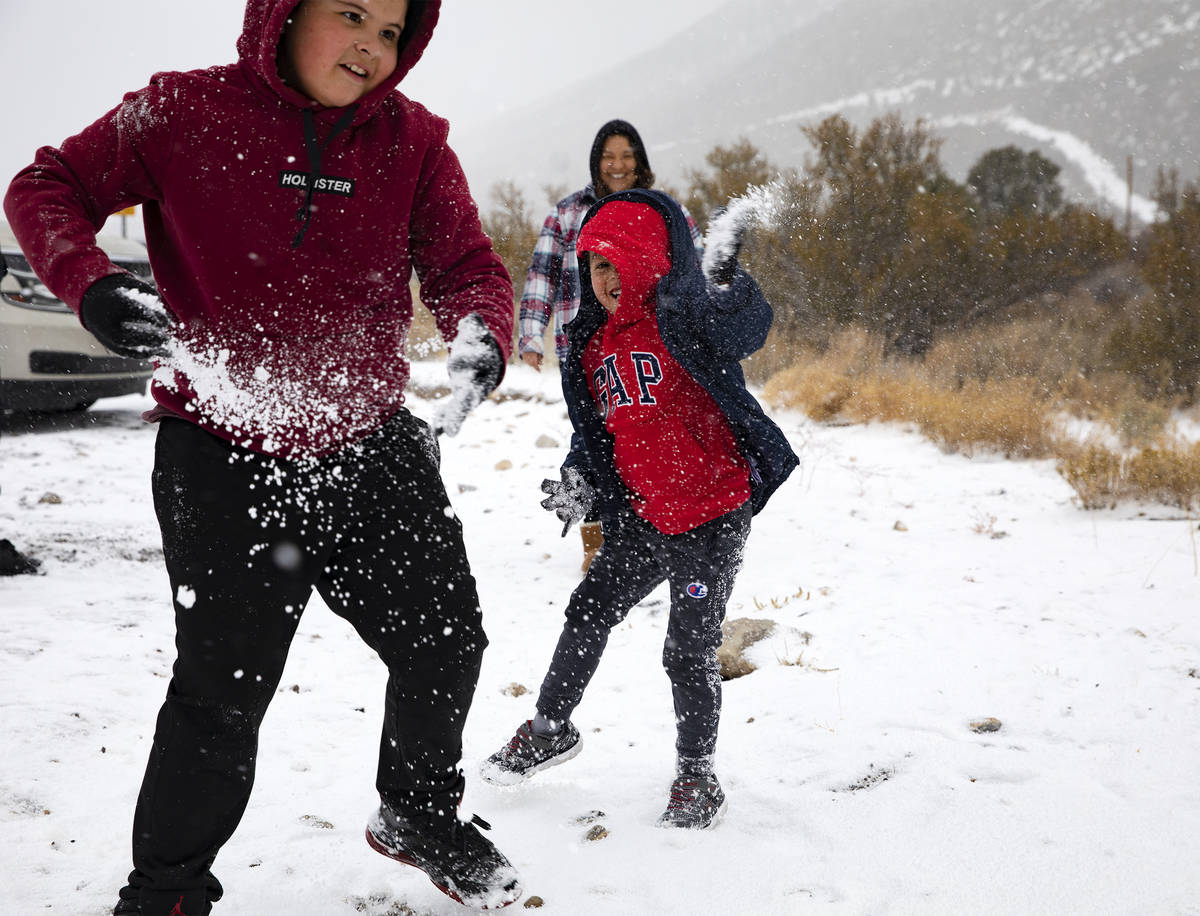 Joan Vasquez, 5, throws a snowball at his brother Max Vasquez, 10, as they play at Mt. Charlest ...
