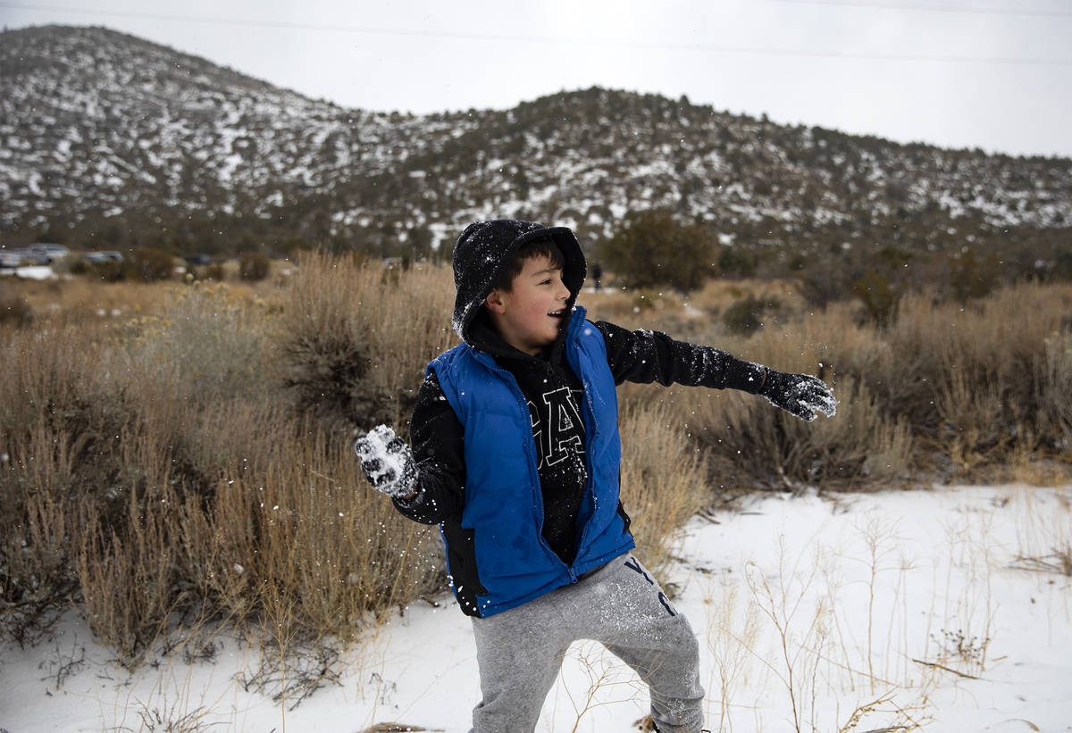 Aaron Vasquez, 8, throws a snowball while playing with his brothers at Mt. Charleston, Sunday, ...