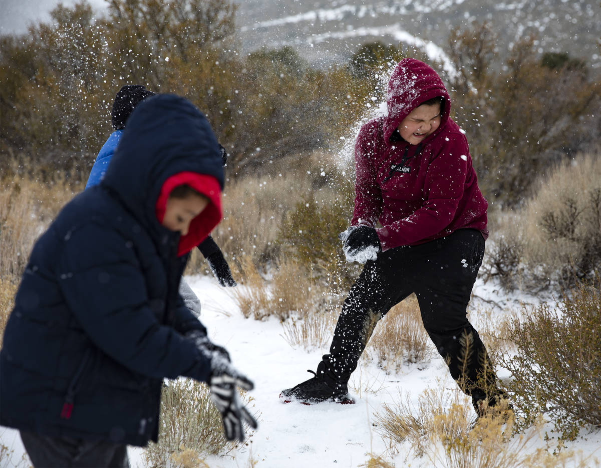 Aaron Vasquez, 8, throws a snowball at his brother Max Vasquez, 10, as they play at Mt. Charles ...