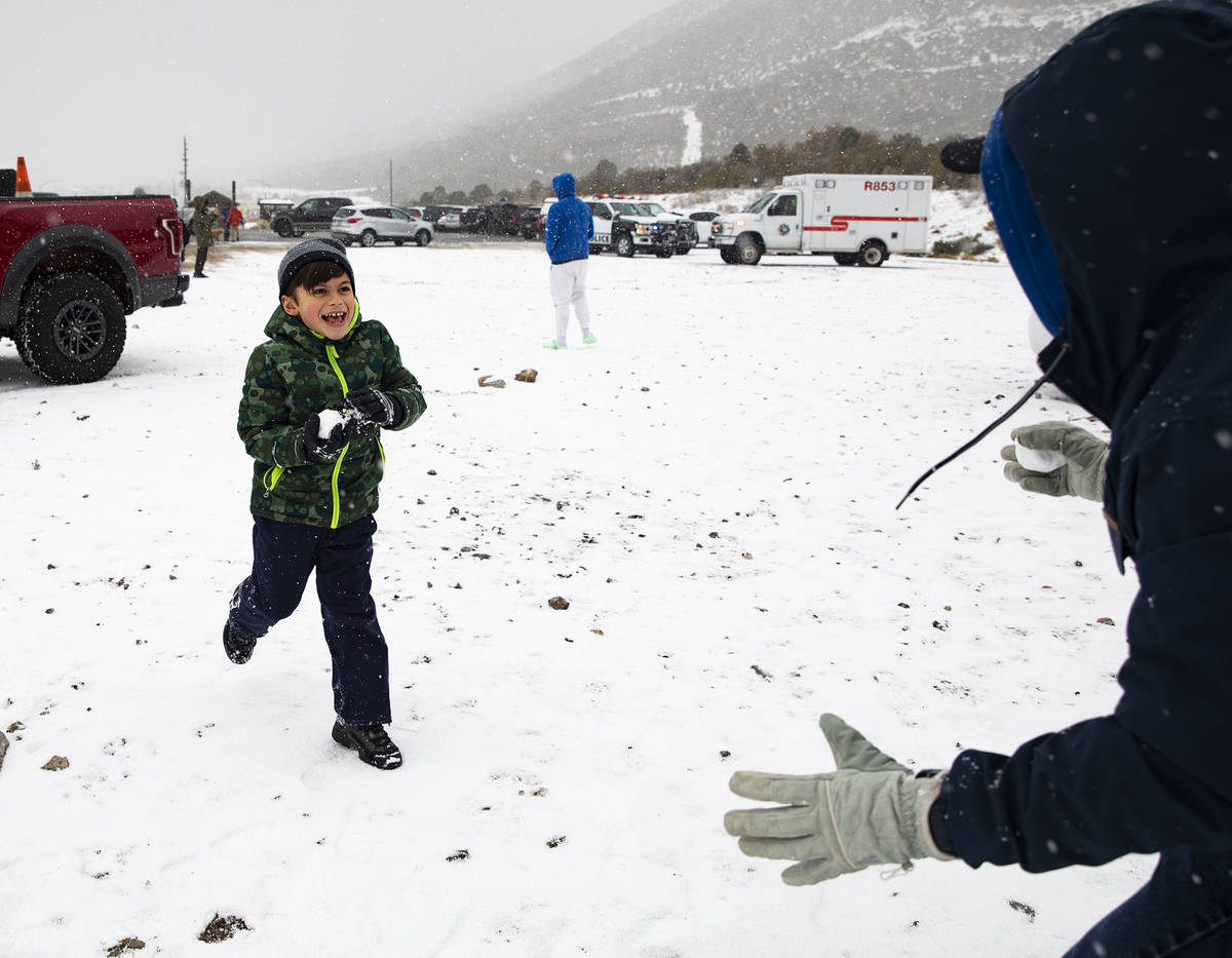 Marshall Byrd, 7, runs towards his dad Tyler Byrd with a snowball at Mt. Charleston on Sunday, ...