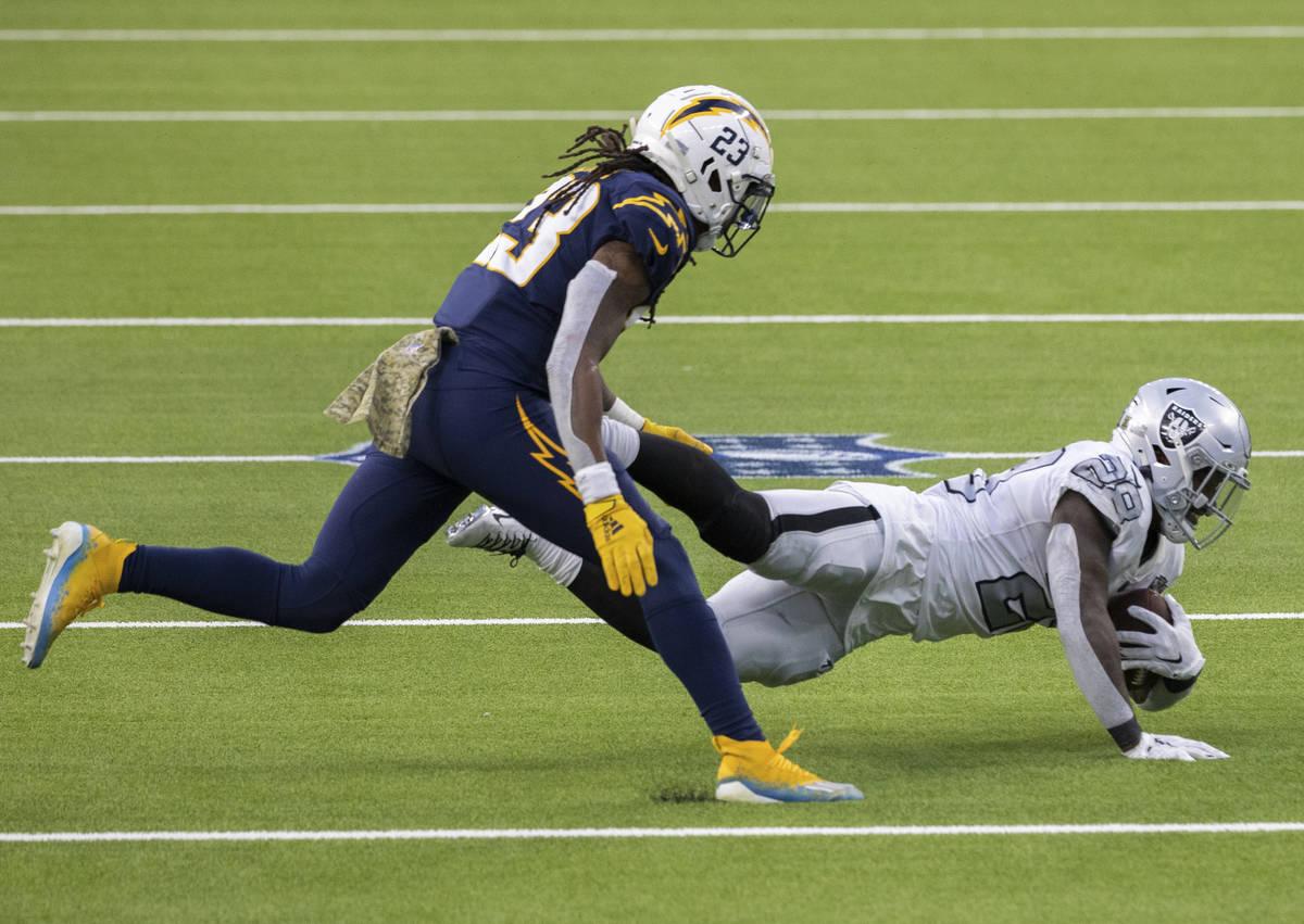 Las Vegas Raiders running back Josh Jacobs (28) leaps forward for extra yardage past Los Angele ...