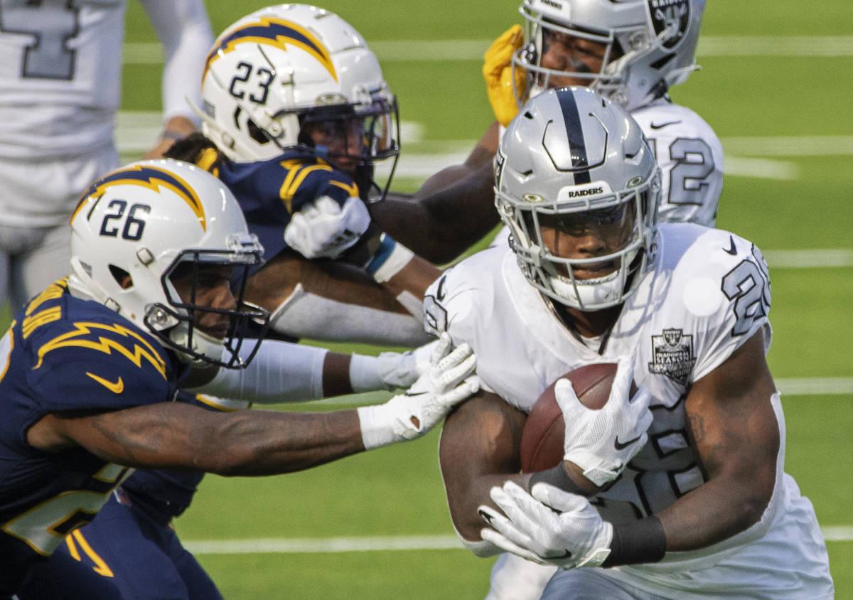 Las Vegas Raiders running back Josh Jacobs (28) breaks through the arm tackles of Los Angeles C ...