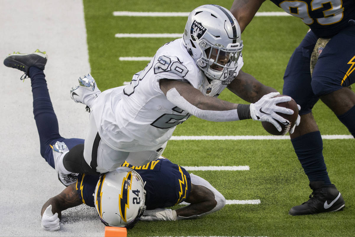 Las Vegas Raiders running back Josh Jacobs (28) leaps into the end zone over Los Angeles Charge ...
