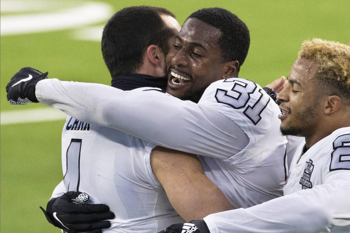 Las Vegas Raiders cornerback Isaiah Johnson (31) gets a hug from Las Vegas Raiders quarterback ...