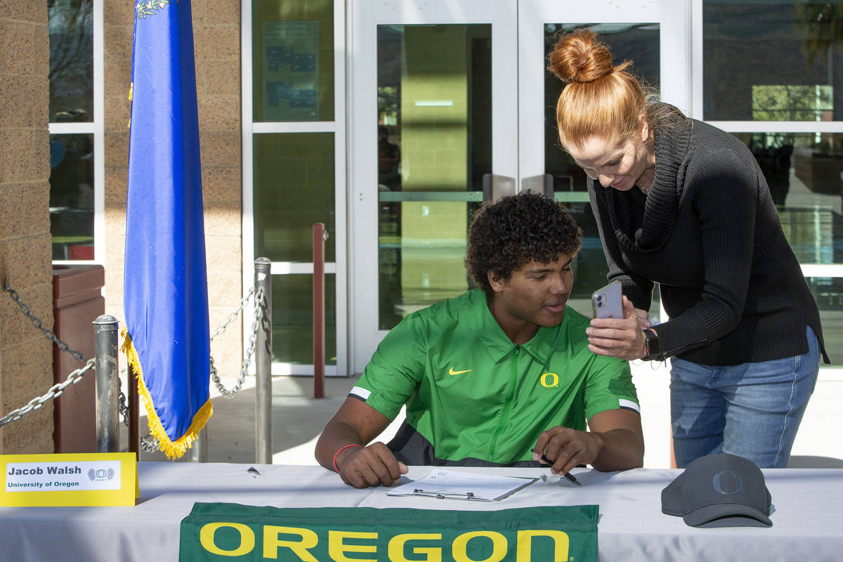 Jacob Walsh, who will play baseball for University of Oregon, looks at photos with his mother, ...