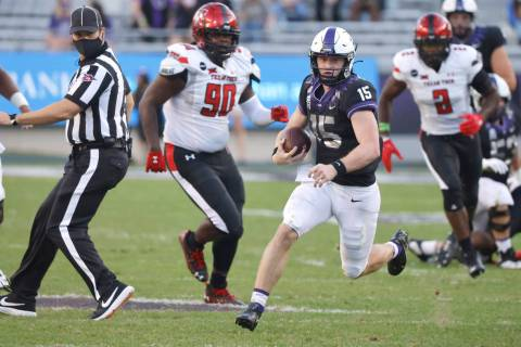 TCU quarterback Max Duggan (15) carries the ball for a first down past Texas Tech defensive lin ...
