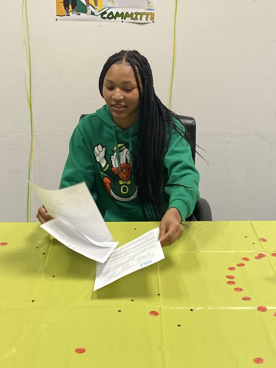 Centennial guard Taylor Bigby signs with Oregon on Wednesday night at the Centennial Hills YMCA ...