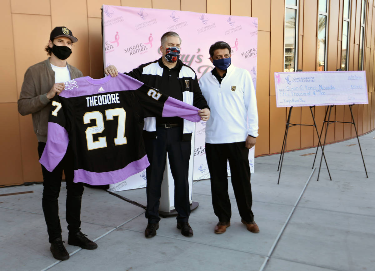 Golden Knights defenseman Shea Theodore, left, CEO of Comprehensive Cancer Centers Jon Bilstein ...