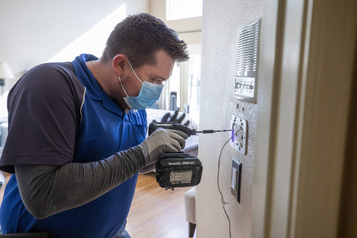 ADT Custom Home Services installation manager Chase Errett installs a security system in a home ...