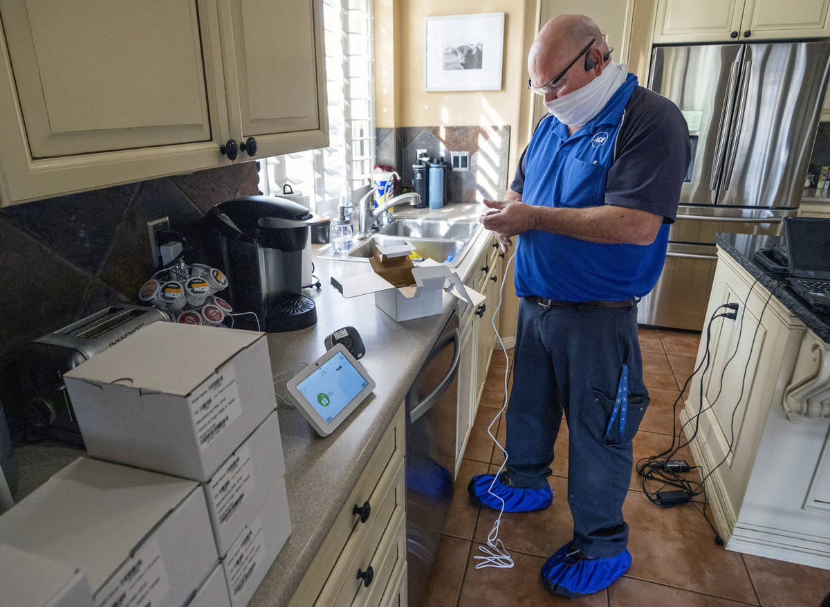 ADT Custom Home Services field service technician Paul Keplinger installs a security system in ...