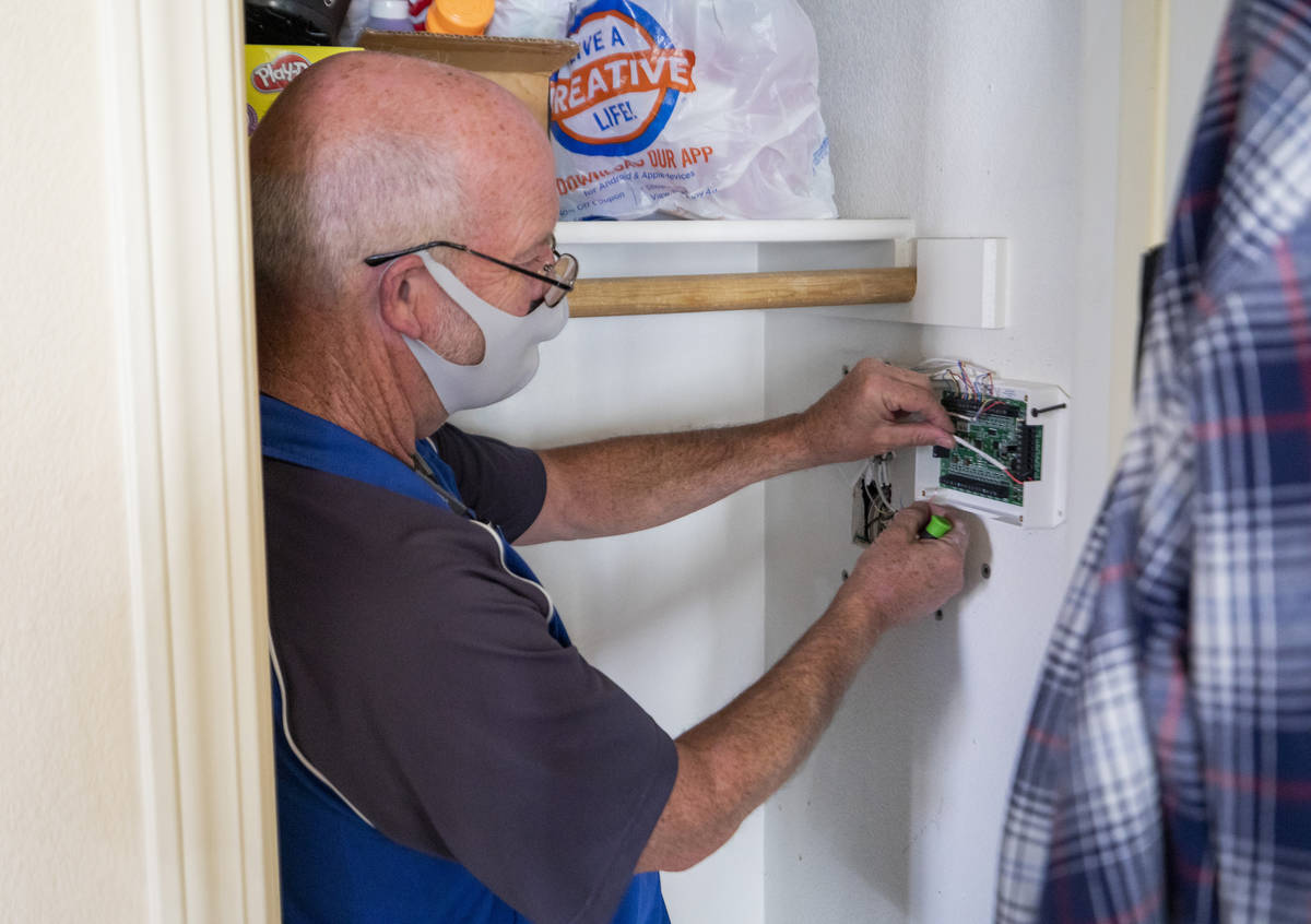 ADT Custom Home Services field service technician Bryant Grieson installs a security system in ...