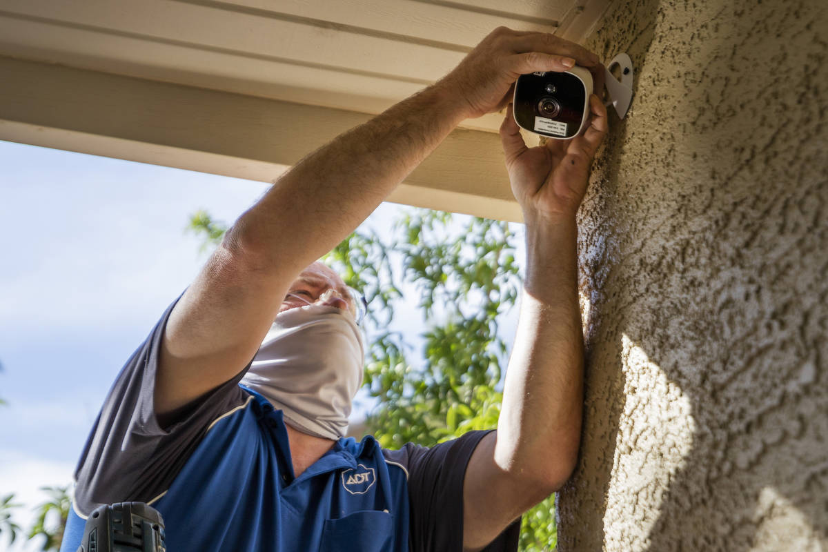 ADT Custom Home Services field service technician Paul Keplinger installs an outdoor security c ...