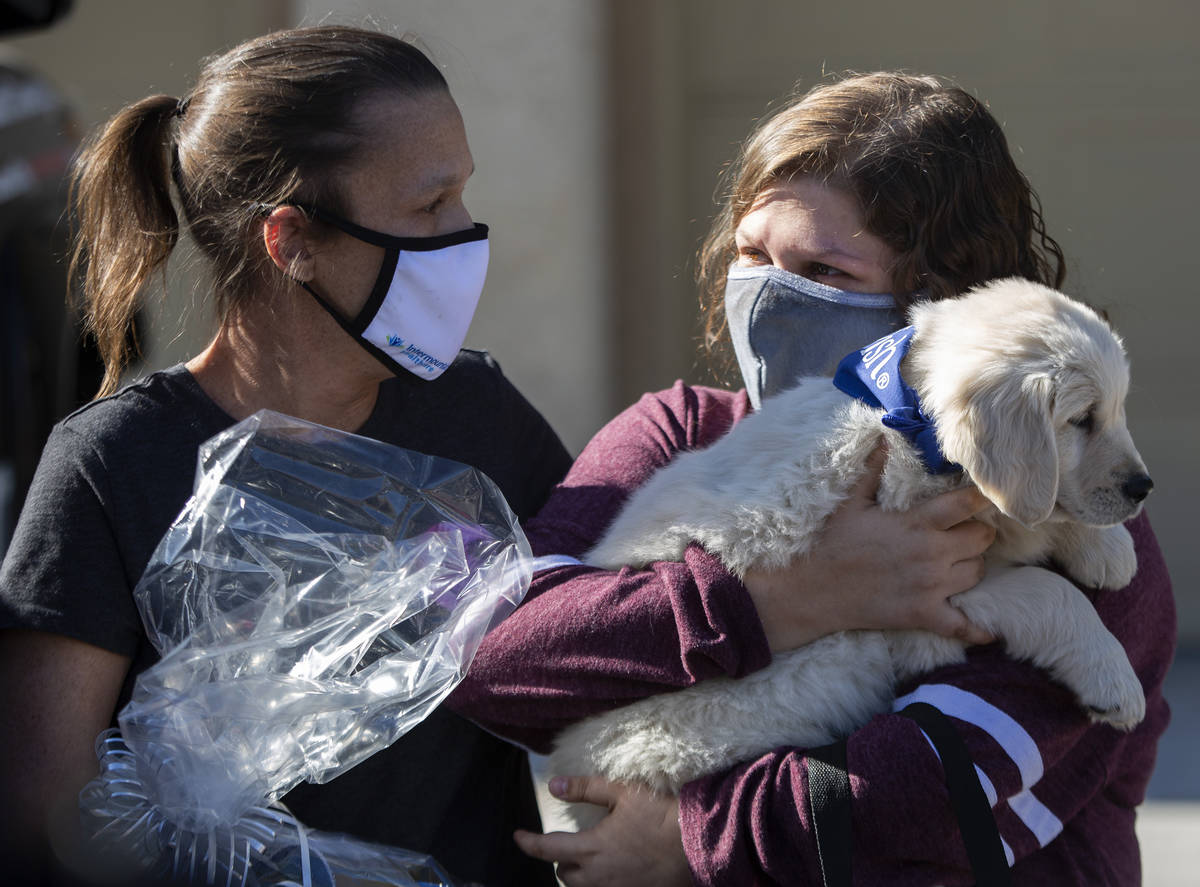 Eighteen-year-old Las Vegan Lauren Cleveland holds her new puppy next to her mother Stephanie a ...