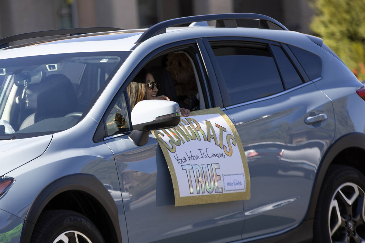 A car parade passes Las Vegan Lauren Cleveland, who received a new puppy from Make-A-Wish South ...