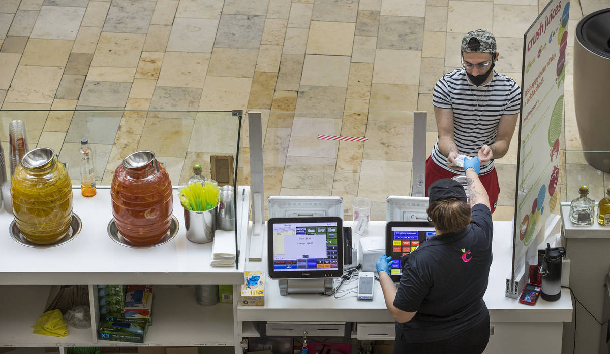 Shopper Jaden King, above, makes a purchase from Jessica Gutierrez at Crush Juices within the F ...
