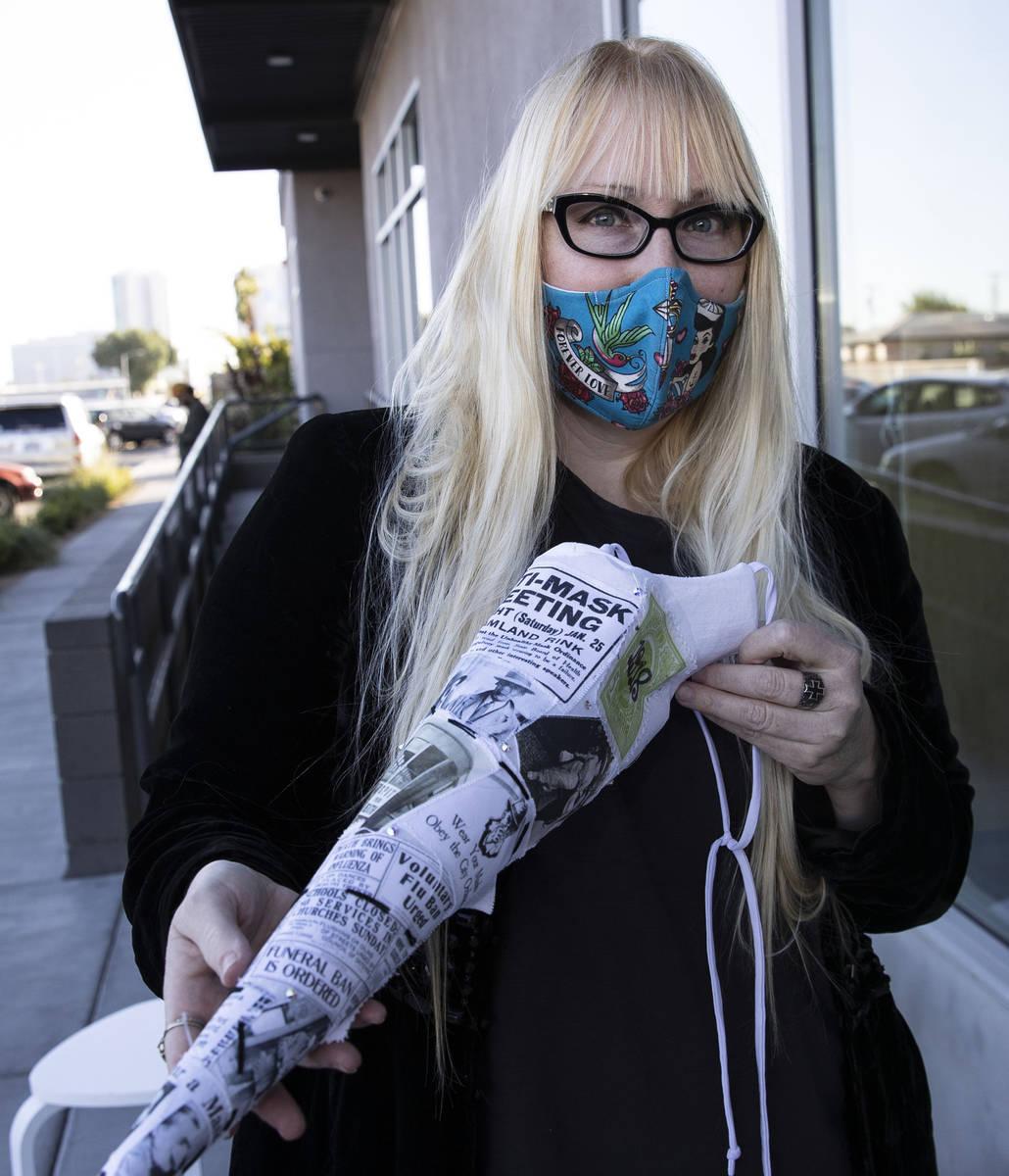 "A local fashion designer, Anna Bartoletti, shows off her ""Full Circle"" mask as she ..."