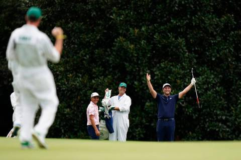 Rickie Fowler, left, watches as Jon Rahm celebrates after making a hole-in-one on the 16th hole ...