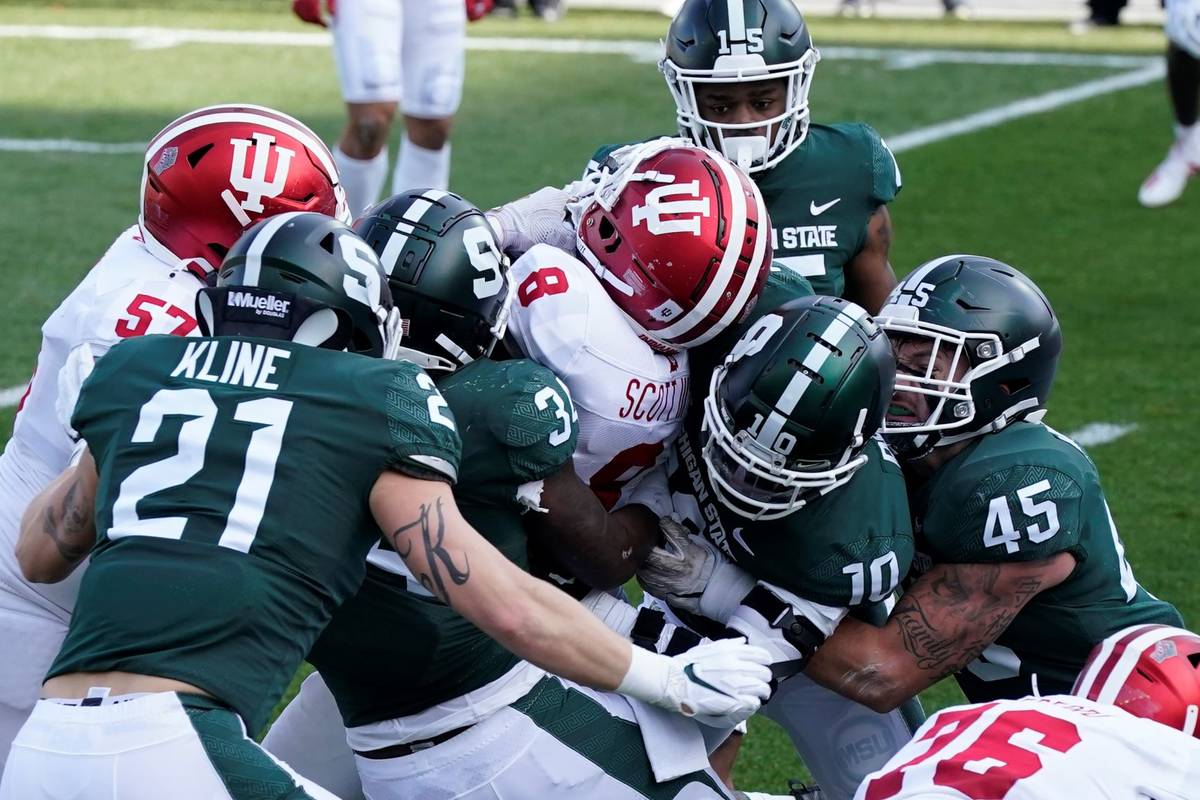 Indiana running back Stevie Scott III (8) is tackled by the Michigan State defense as he falls ...