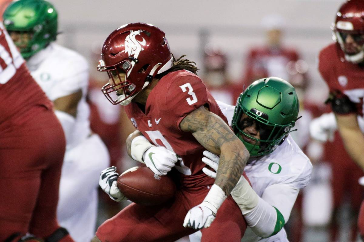 Oregon linebacker Noah Sewell, right, tackles Washington State running back Deon McIntosh durin ...