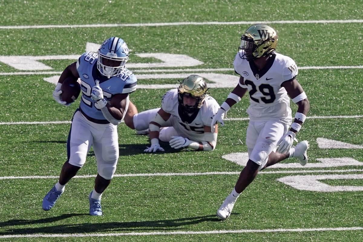 North Carolina running back Javonte Williams (25) runs while Wake Forest defensive back Caelen ...