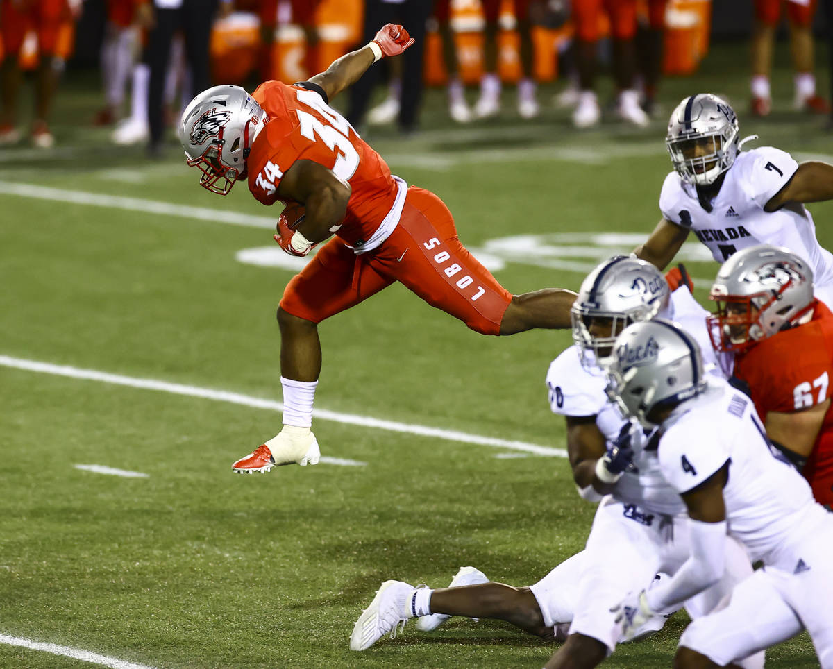 New Mexico Lobos running back Bobby Cole (34) jumps over UNR defenders during the second half o ...