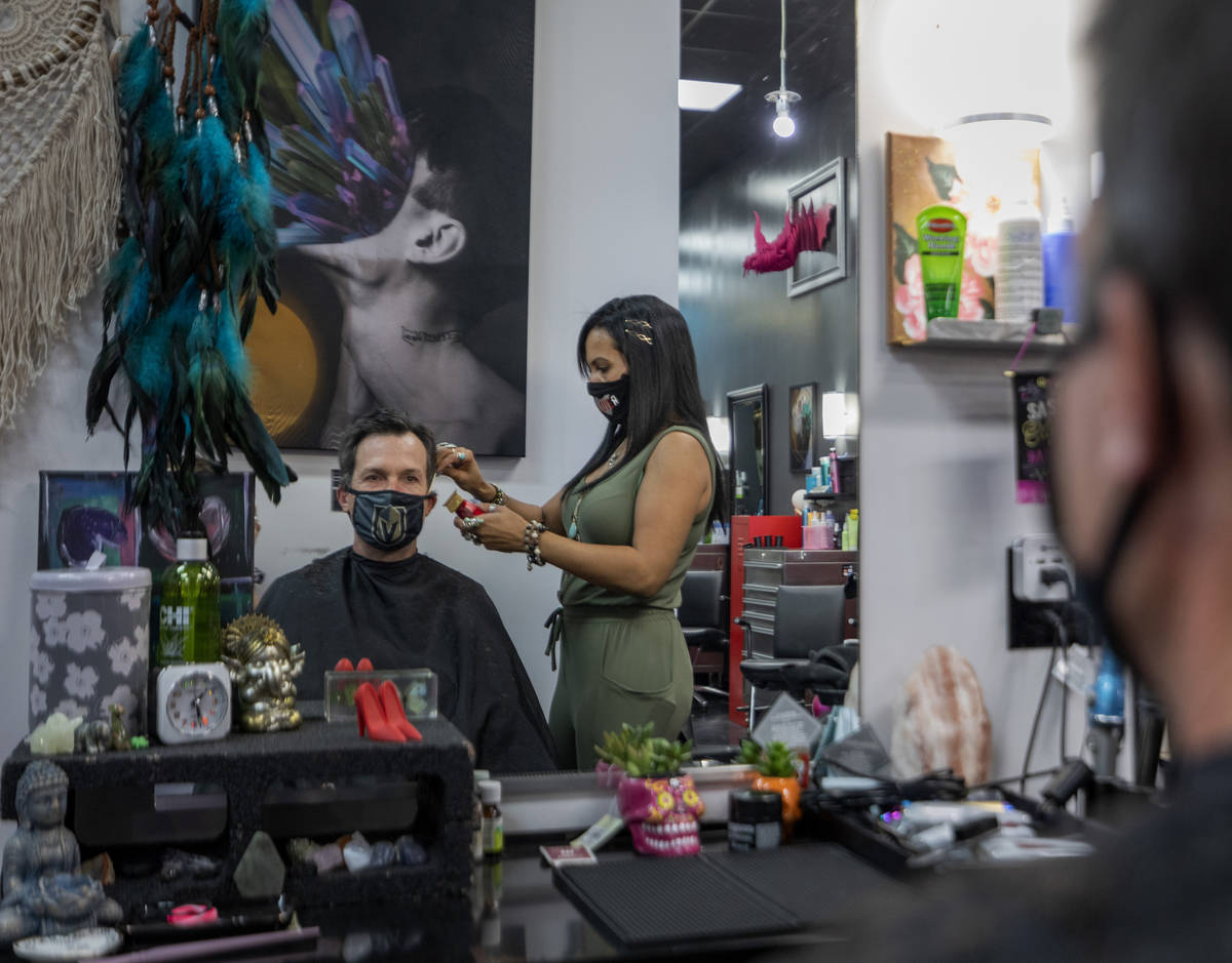 Client Mike Longi, 56, of Las Vegas, receives a hair cut by stylist and creative director of Re ...