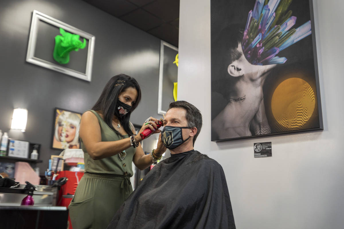 Stylist and creative director of Revolution Salon Lilia Dryer gives a hair cut to Mike Longi, 5 ...