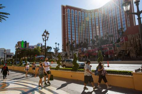 People walk down the Strip in front of Treasure Island in Las Vegas on Friday, July 3, 2020. (L ...