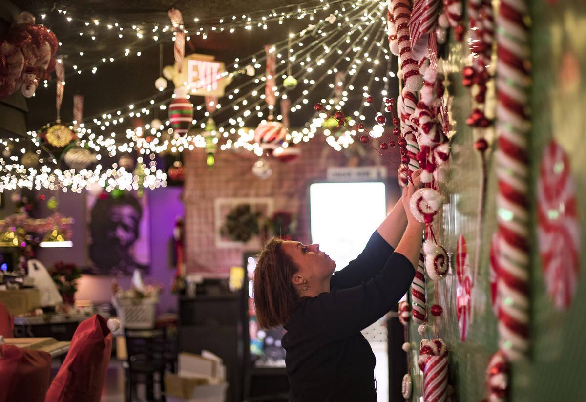 Sara Kiper decorates a wall at the Sand Dollar Lounge in Las Vegas, Monday, Nov. 25, 2019. The ...