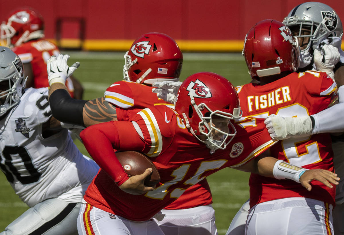 Kansas City Chiefs quarterback Patrick Mahomes (15) tries to scramble away from Las Vegas Raide ...