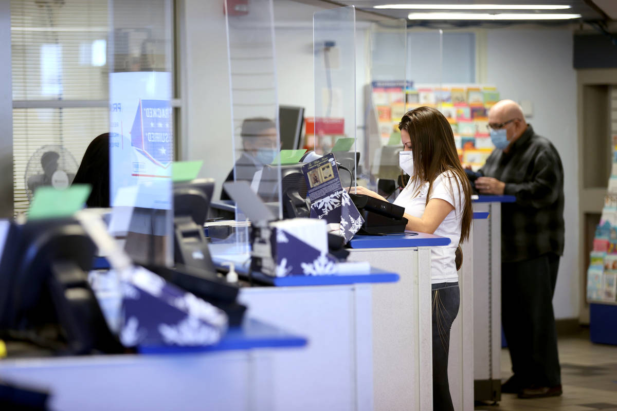 Clerks help customers at the main Las Vegas Post Office on Sunset Road Wednesday, Nov. 25, 2020 ...