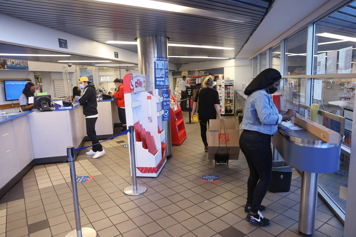 Customers, including Tasha Austin of Henderson, right, ship packages at the main Las Vegas Post ...