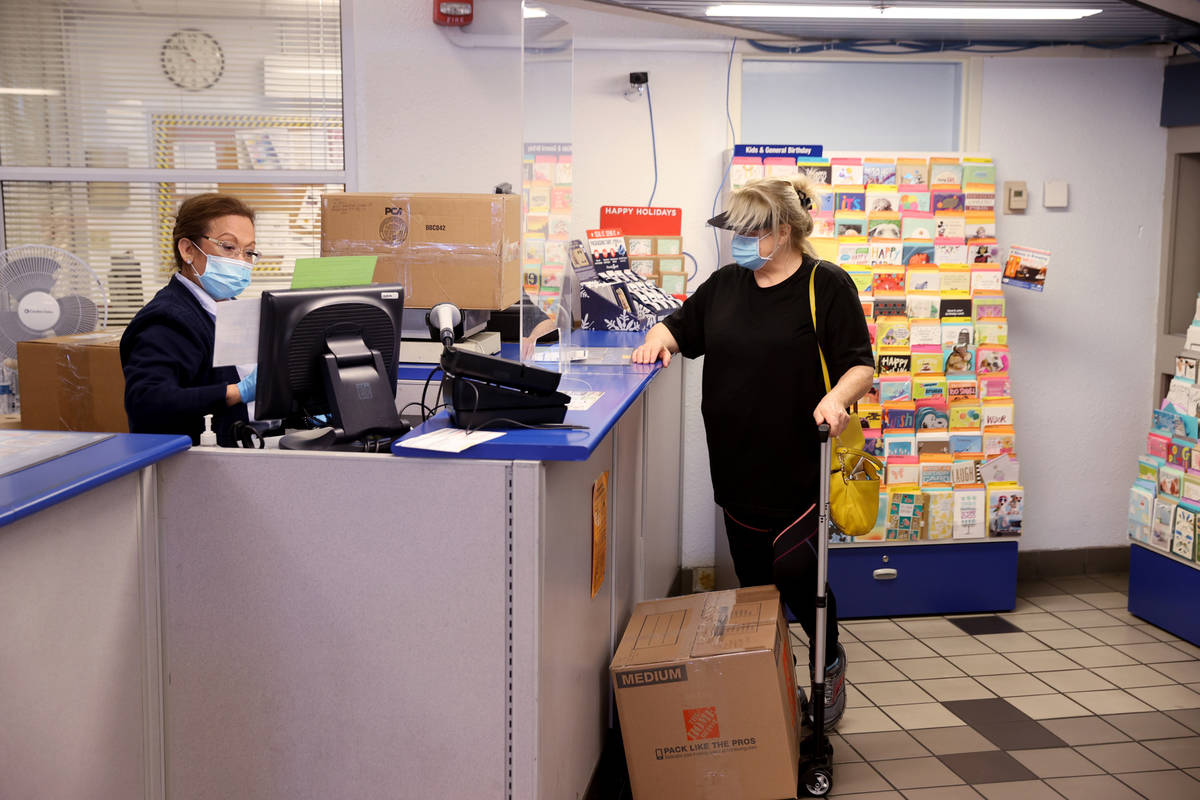 Imelda Brown helps a customer who declined to give her name ship packages at the main Las Vegas ...