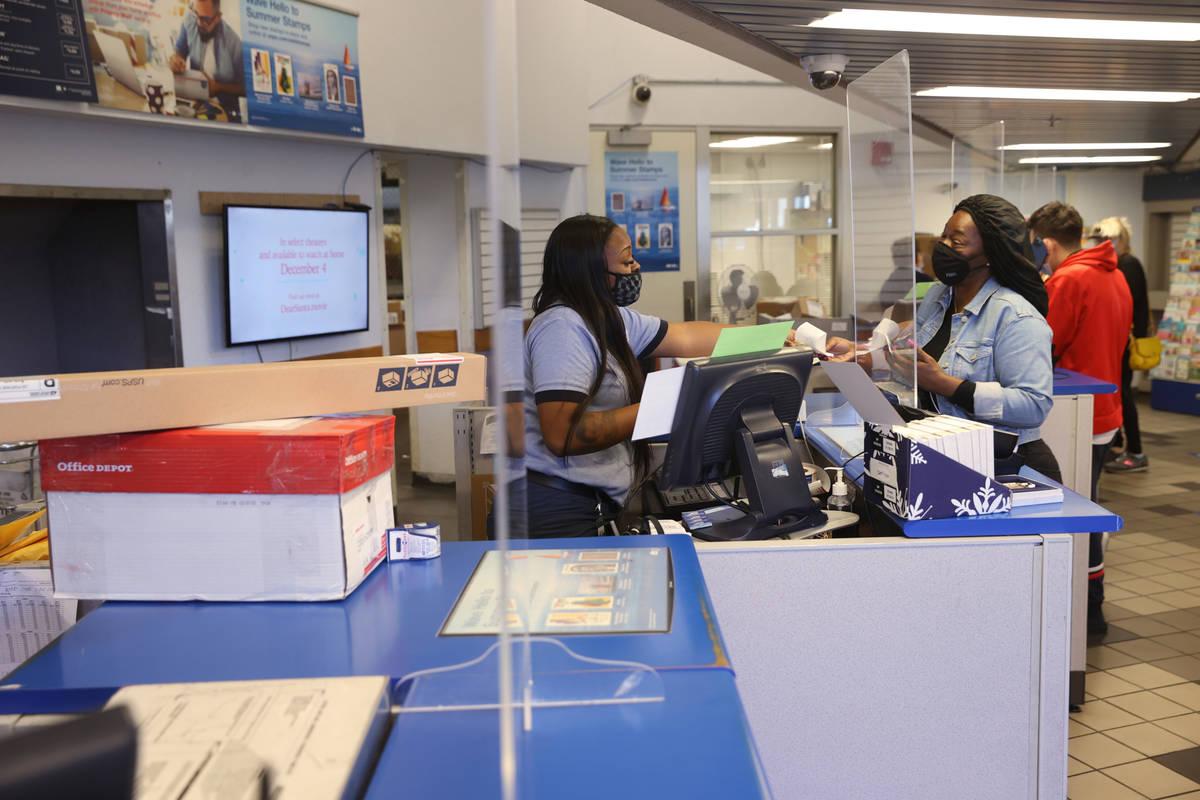 Prenciss Rogers helps Tasha Austin of Henderson at the main Las Vegas Post Office on Sunset Roa ...