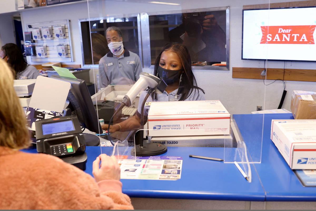 Marson Dent helps Kim Leddon of Phoenix ship packages at the main Las Vegas Post Office on Suns ...