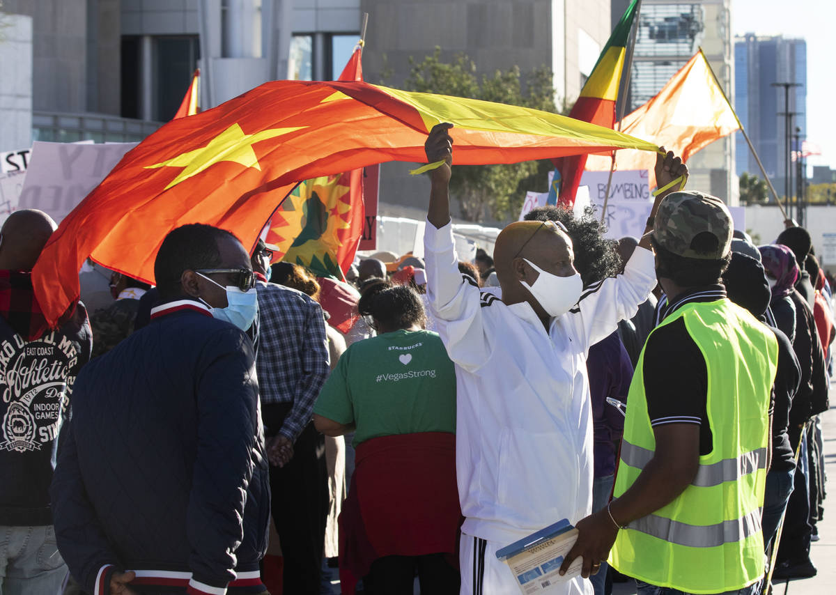 Gebrekidan Desita, center, holds a flag of Tigray outside of the Lloyd D. George Federal Courth ...
