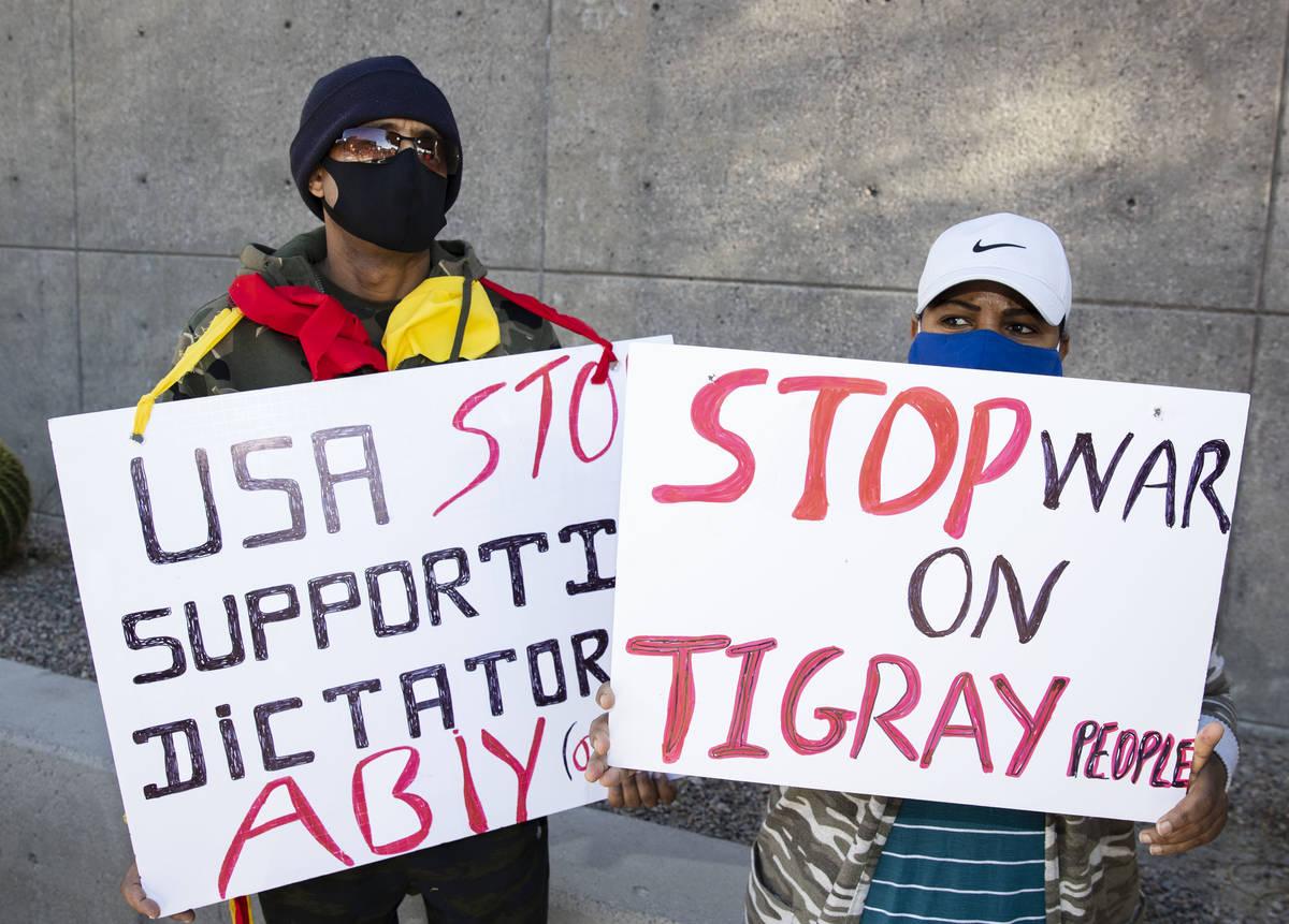 Samson Araya, left, and Senait Negussie hold signs outside of the Lloyd D. George Federal Court ...