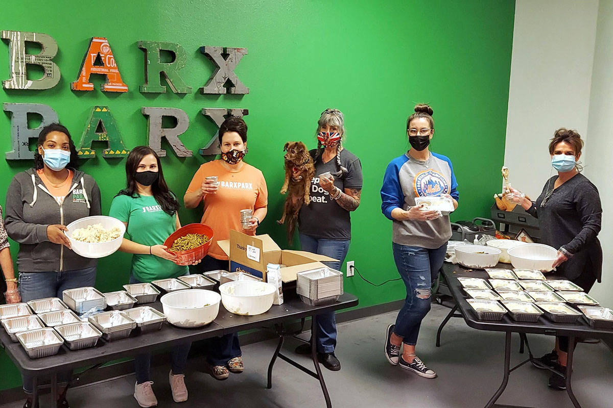 "An assembly line of volunteers on Sunday, Nov. 22, 2020, preps ""PUPsgiving"" meals inside Barx P ..."