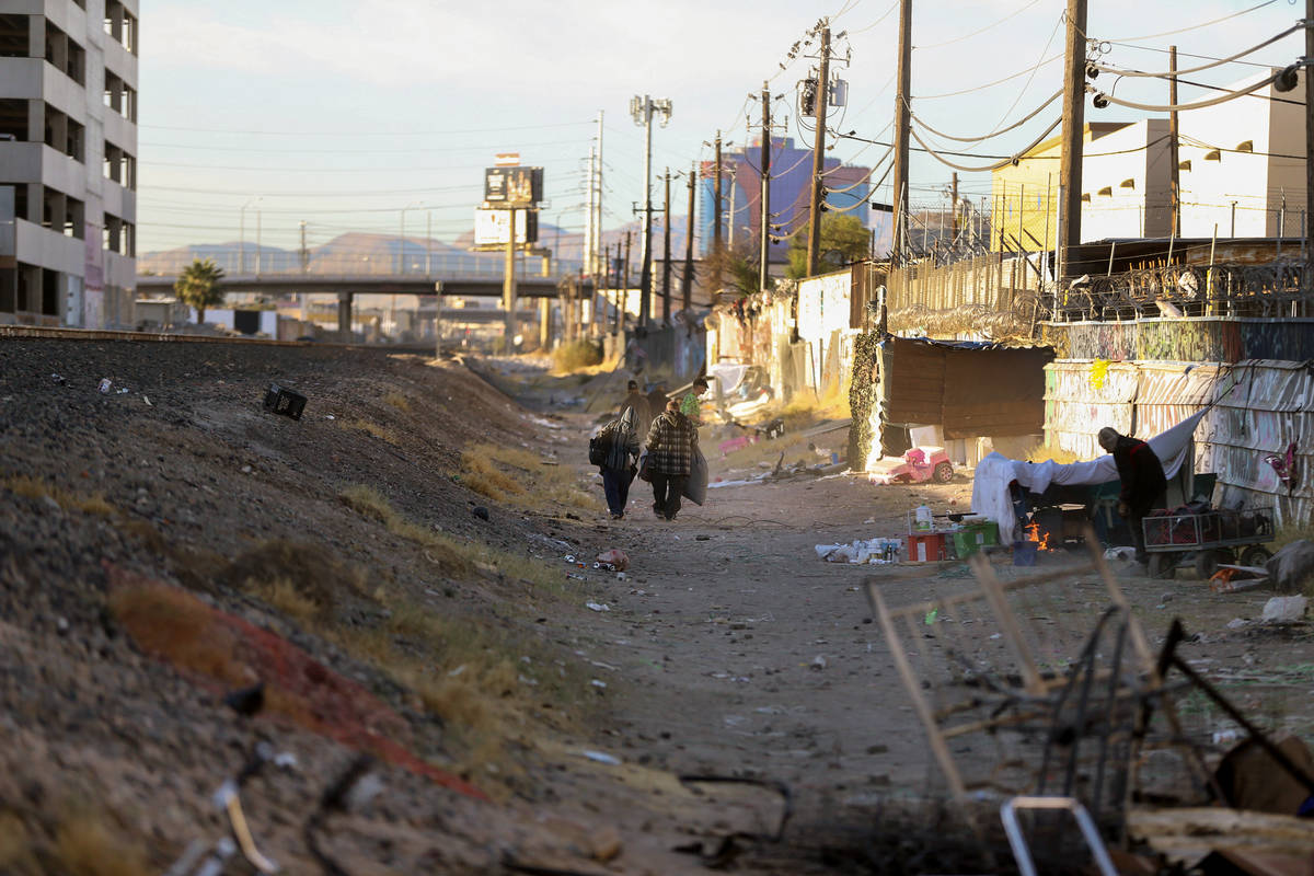 People walk along the train tracks near Oakey Boulevard and Highland Drive in Las Vegas on Nov. ...