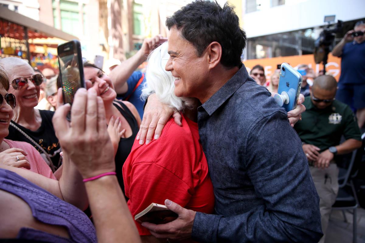 Strip headliner Donny Osmond hugs Kim Lemons of Sterling, Okla. after receiving a Key to The La ...
