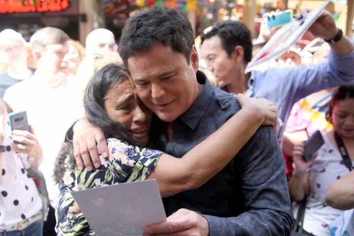 Strip headliner Donny Osmond hugs Lucie Hanna of Canoga Park, Calif., after receiving a Key to ...