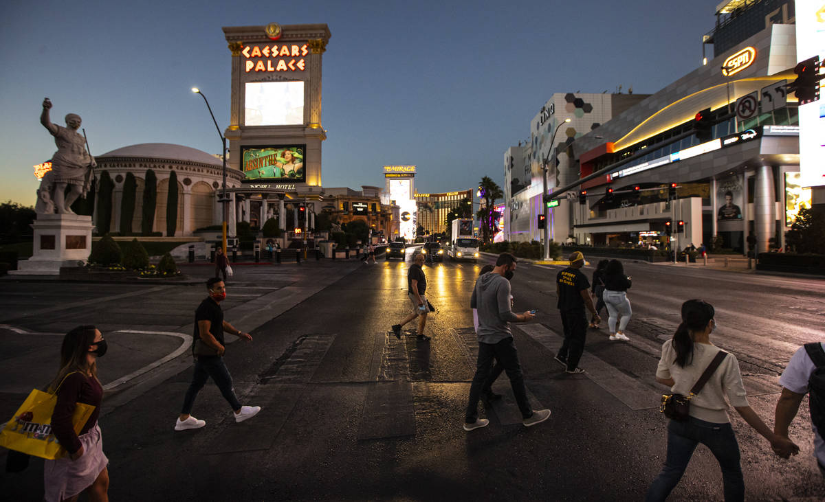 People cross the Las Vegas Strip outside of Caesars Palace and The Linq Hotel Thursday, Nov. 19 ...