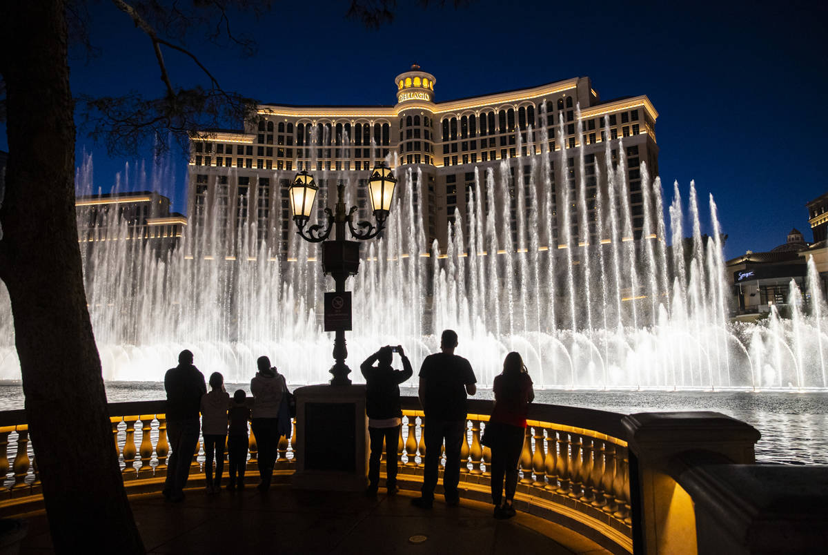 People watch the Bellagio fountain show on the Las Vegas Strip Thursday, Nov. 19, 2020. (Chase ...