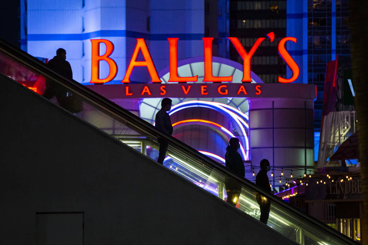 People are silhouetted by a sign for Bally's as they descend an escalator from a pedestrian bri ...