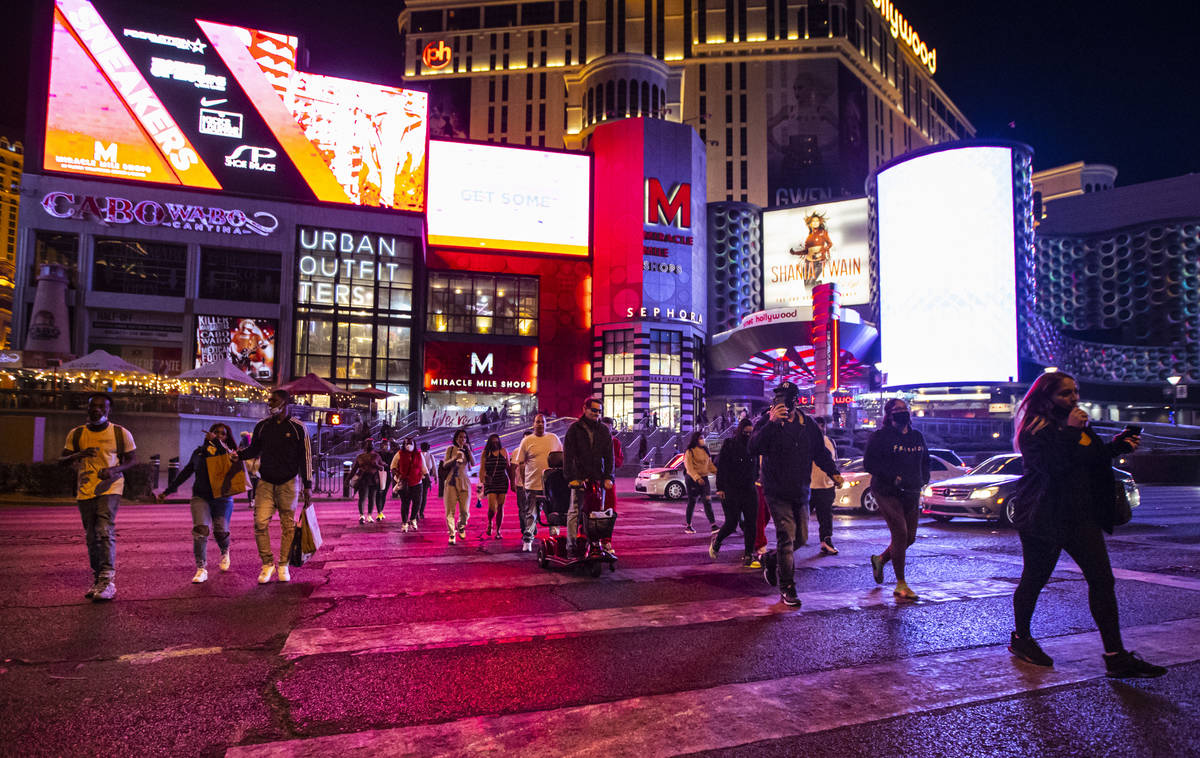 People walk along a crosswalk outside of the Miracle Mile Shops on the Las Vegas Strip Thursday ...