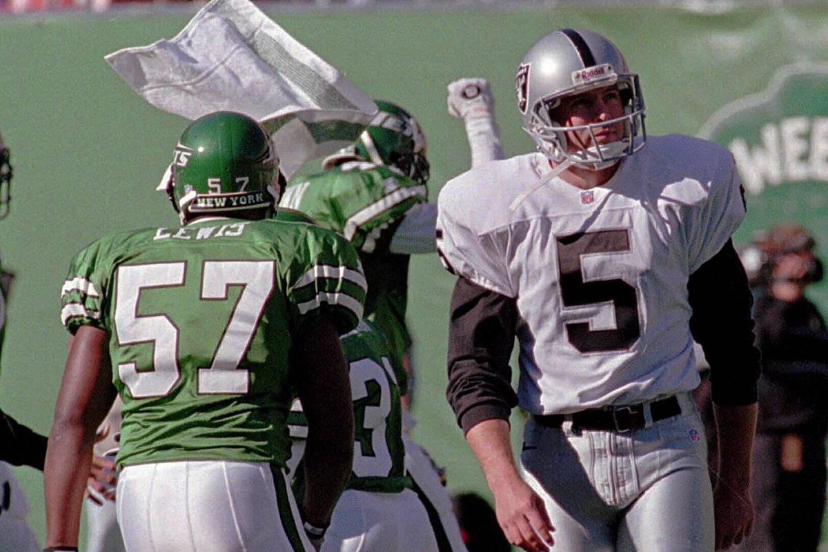 Oakland Raiders kicker Cole Ford (5) turns away as New York Jets' Mo Lewis (57) and other teamm ...
