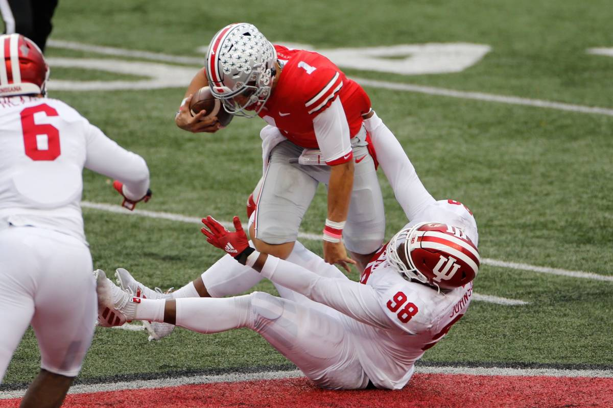 Indiana defensive lineman Jerome Johnson, bottom, sacks Ohio State quarterback Justin Fields du ...