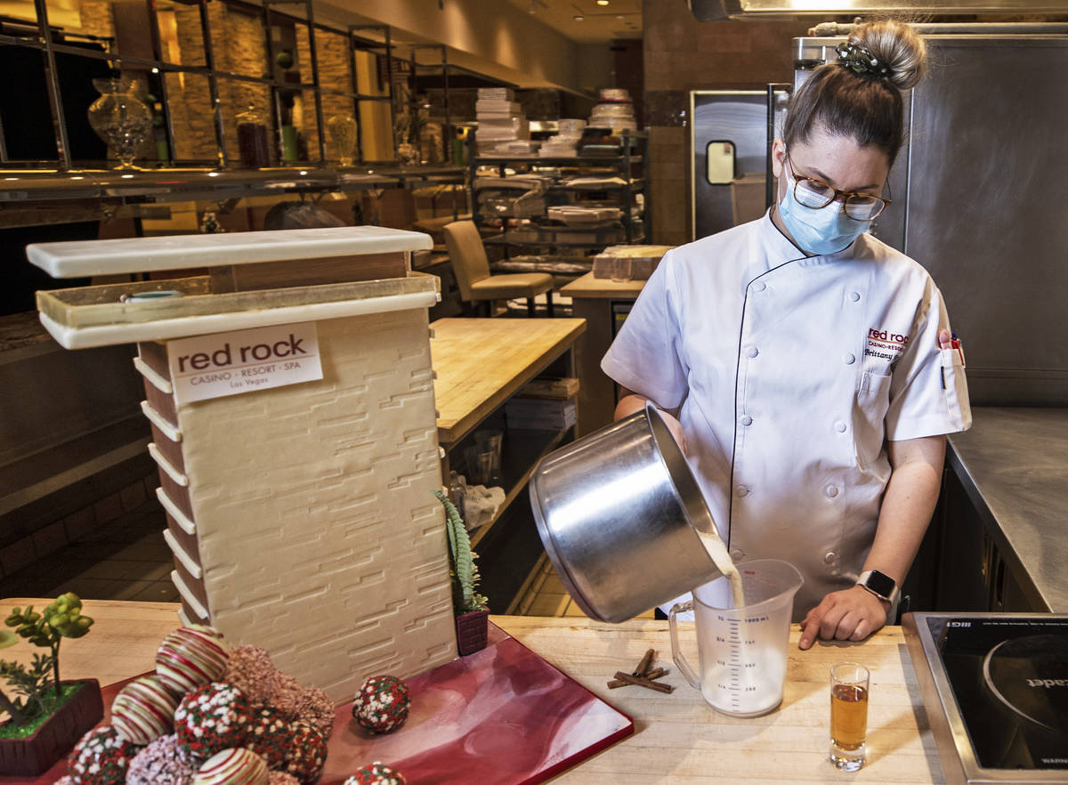 Pastry chef Brittany Simmons measures out 8 oz. of boiling milk in preparation to make a hot co ...