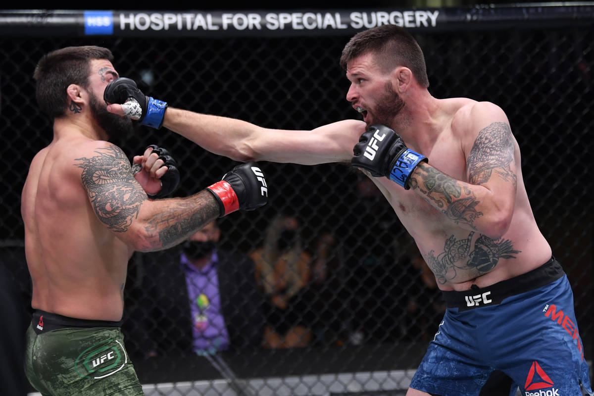 LAS VEGAS, NEVADA - NOVEMBER 21: (R-L) Tim Means punches Mike Perry in their welterweight bout ...